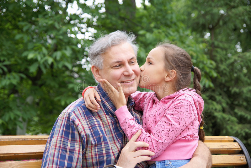 Daughter kissing her father stock photography
