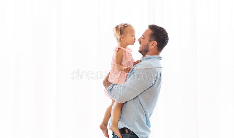Daughter kissing her father sitting on his hands royalty free stock images