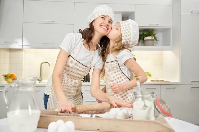 Daughter kissing mom, while cooking pastry in kitchen. stock photo