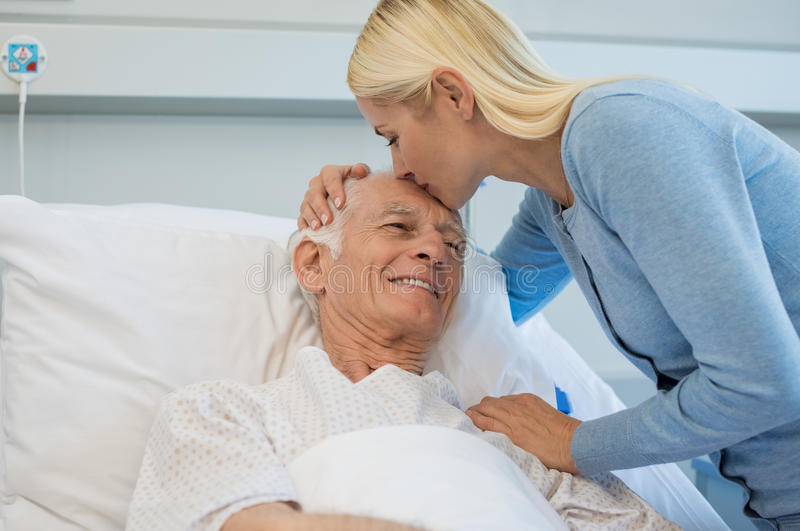 Daughter kissing senior father. Young daughter kissing senior father on forehead in hospital bed. Cheerful old dad patient being kissed by daughter while royalty free stock photography