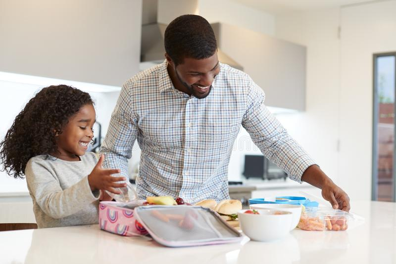 Daughter In Kitchen At Home Helping Father To Make Healthy Packed Lunch royalty free stock photos