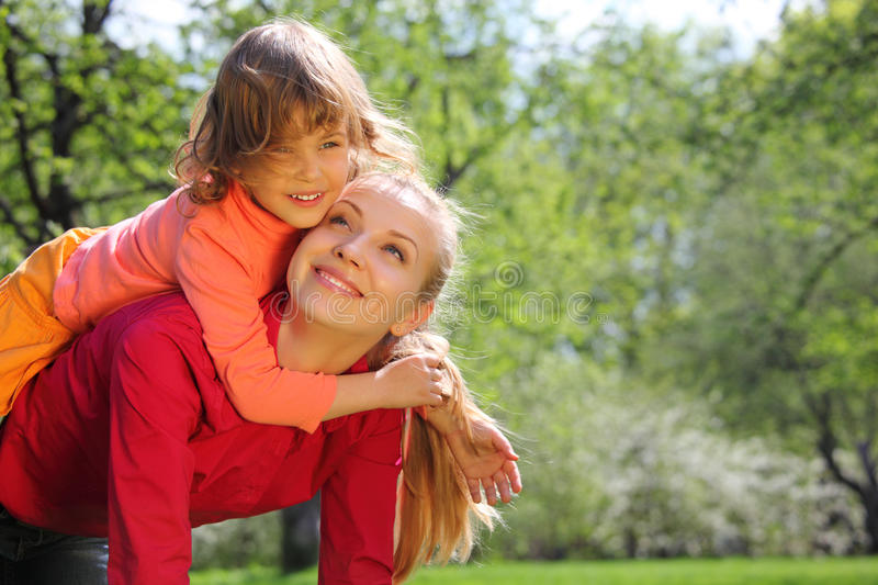 Download Daughter Lies At Mother On  Back In Spring Stock Photo - Image of girl, outdoor: 9873066