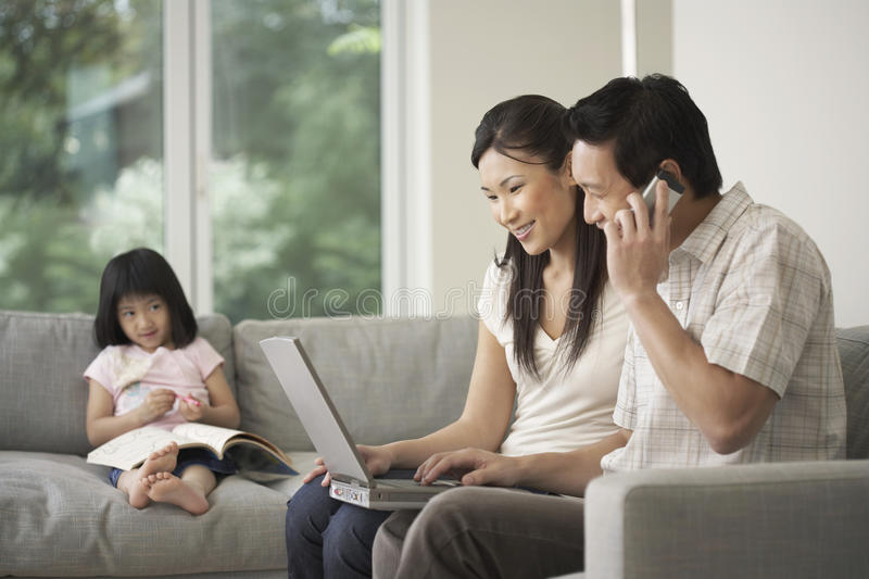 Daughter Looking At Couple Use Laptop And Cellphone royalty free stock image