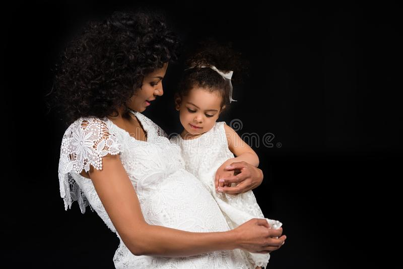 Daughter looking at pregnant mothers belly stock photos