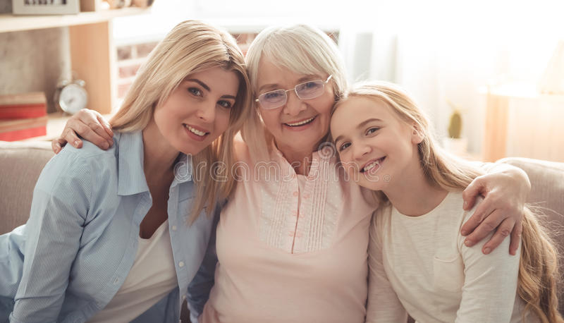 Daughter, mom and granny. Three generations of women. Beautiful granny, mother and daughter are hugging, looking at camera and smiling while sitting on couch at royalty free stock image