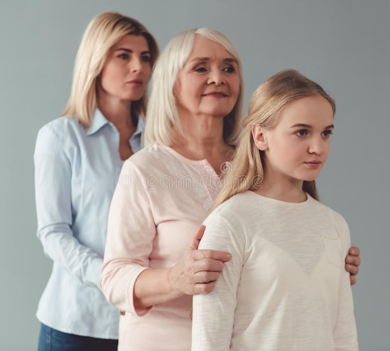 Daughter, mom and granny. Three generations of women. Beautiful granny, mother and daughter are standing one by one on gray background stock photos