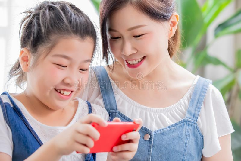 Daughter and mom play mobile game royalty free stock image