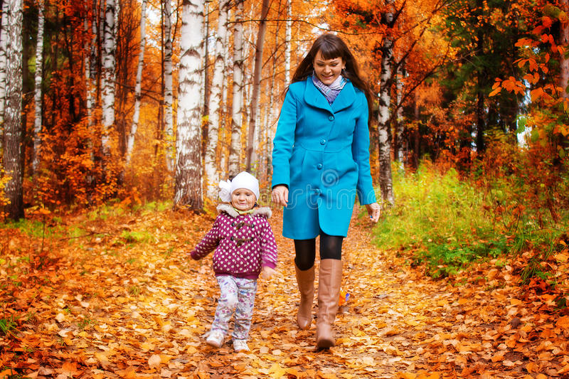 Daughter with mom running in the woods royalty free stock images