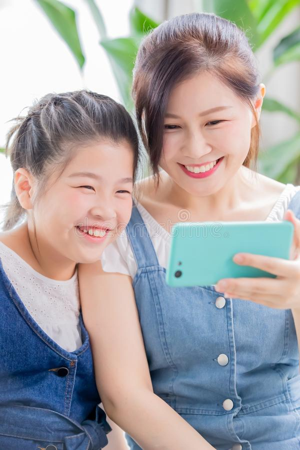 Daughter and mom use smartphone stock photos