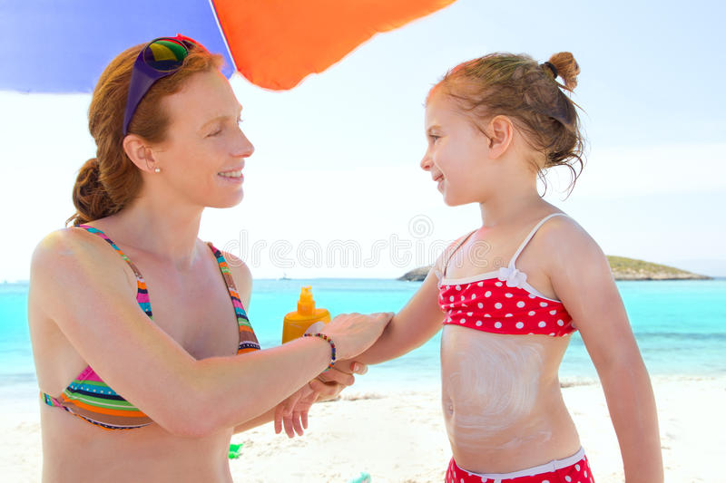 Daughter and mother in beach with sunscreen stock photos