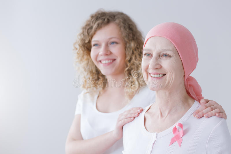 Daughter and mother with breast cancer. Smiling on white background stock photo