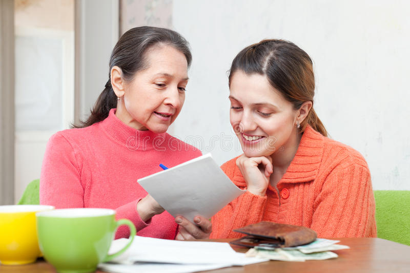 Daughter and mother counts the family budget. Adult daughter and mother counts the family budget at home royalty free stock photos