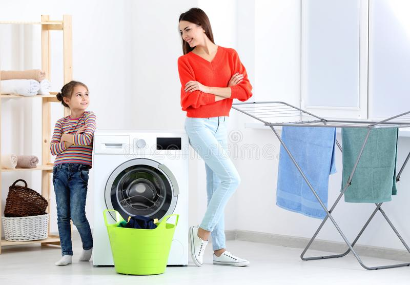 Daughter and mother doing laundry together stock photo