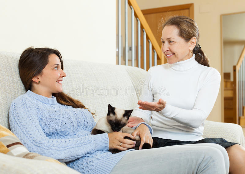 Daughter and mother gossiping on sofa. Smiling teen daughter and mother sitting together on sofa and gossiping royalty free stock photography