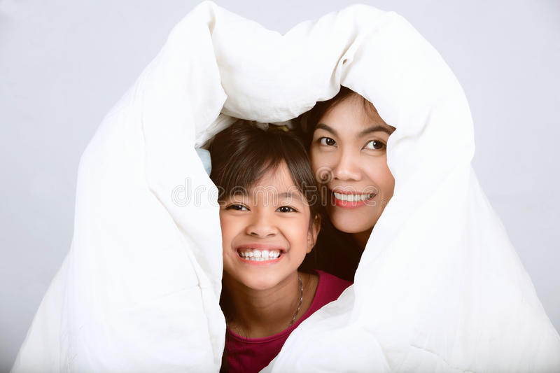 Daughter and mother. Are happy together under the sheets in bedroom royalty free stock photo