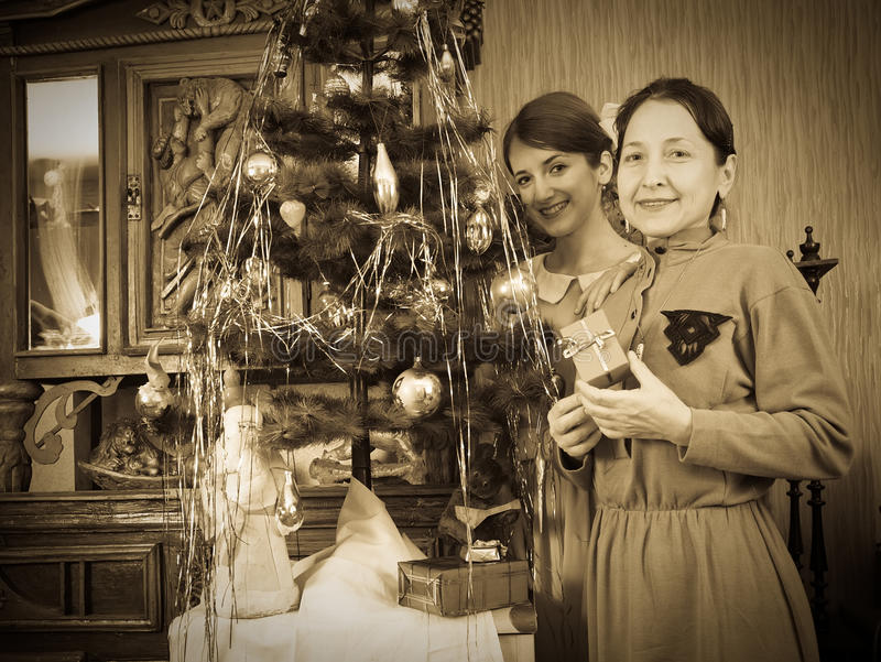 Daughter with mother near Christmas tree