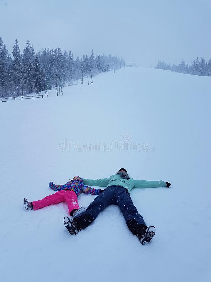 Daughter and mother are playing and lying in the snow in winter outdoors stock image