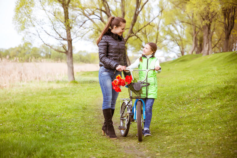 Daughter and mother walk along the shore of the lake with a bike and talk. Family values, education royalty free stock photos