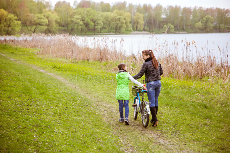Daughter and mother walk along the shore of the lake with a bike and talk. Family values, education royalty free stock image
