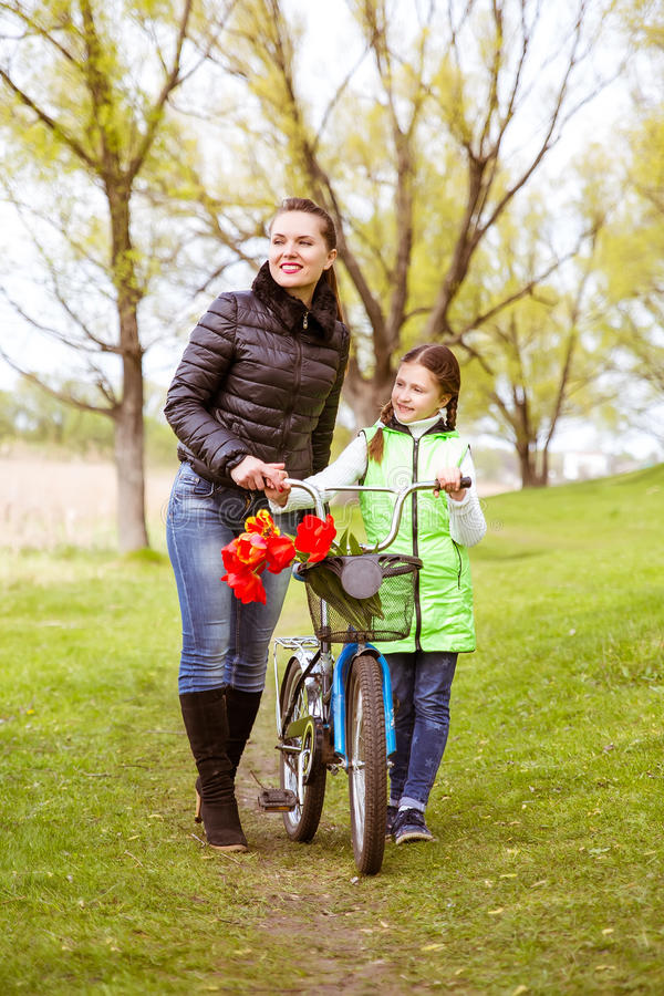Daughter and mother walk along the shore of the lake with a bike and talk. Family values, education stock image