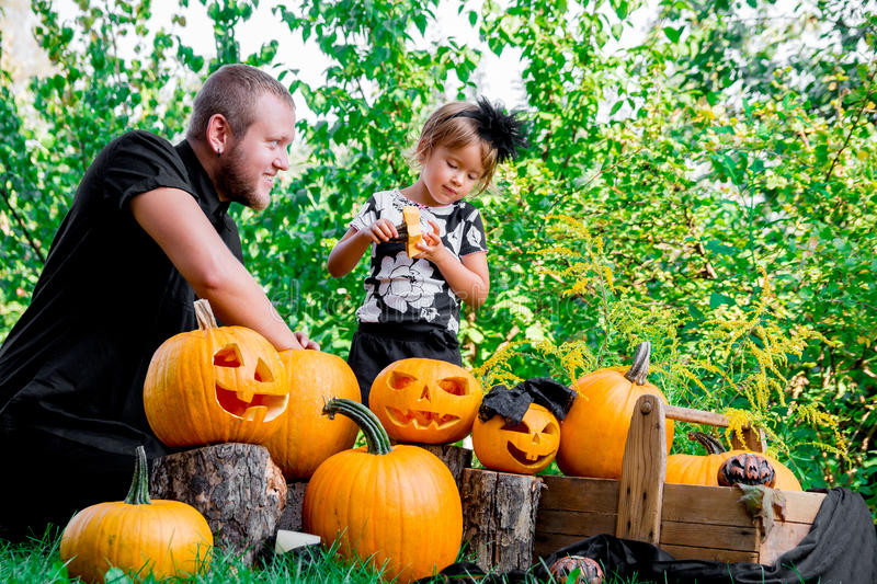 Daughter near father who pulls seeds and fibrous material from a pumpkin before carving for Halloween. Prepares jack-o-lantern. D stock photography