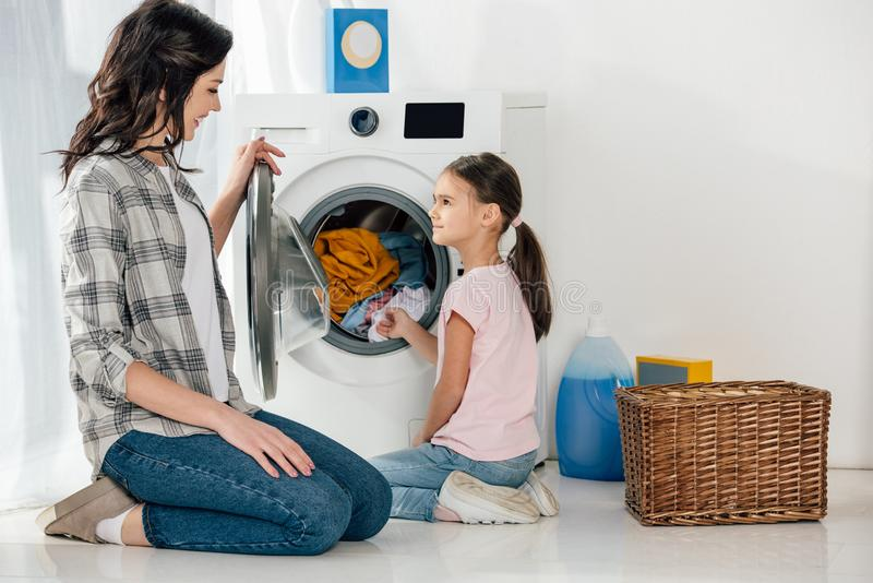 daughter in pink t-shirt and mother in grey shirt sitting on floor near washer with clothes stock images