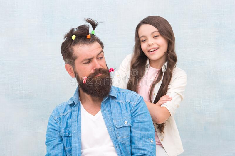 Daughter playing with hair. Ideas to entertain kids during quarantine. Family leisure concept. Girl dad hairdo. Quarantine with children. Happy family. Happy stock image