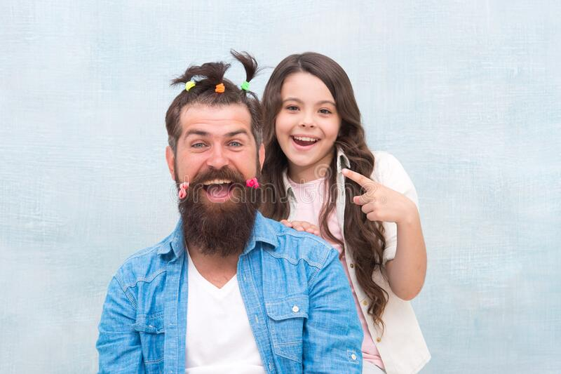 Daughter playing with hair. Ideas to entertain kids during quarantine. Happy childhood. Upbringing happy daughter. Family leisure concept. Girl dad hairdo royalty free stock images
