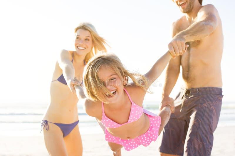 Daughter playing with parents stock photos