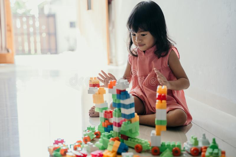 Daughter playing with plastic brick at home. Asian young daughter playing with plastic brick at home by her self royalty free stock images
