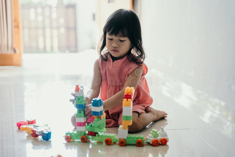 Daughter playing with plastic brick at home. Asian young daughter playing with plastic brick at home by her self stock photos