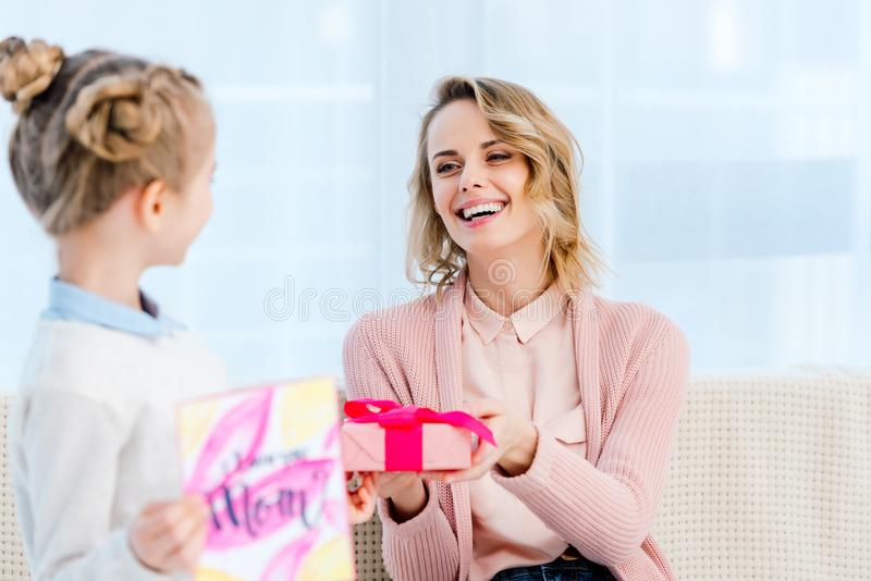 daughter presenting gift box to laughing mother at home on happy stock photos