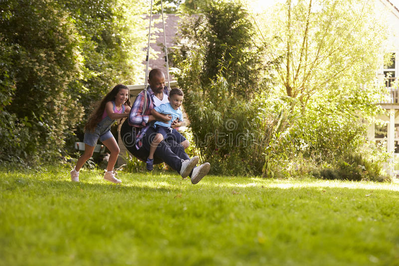 Daughter Pushing Father And Son On Tire Swing In Garden stock image
