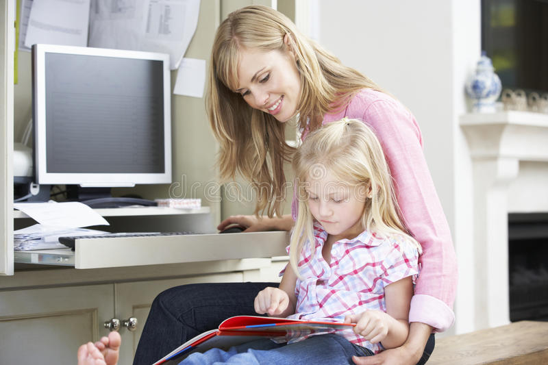 Daughter Reading Book Whilst Mother Works In Home Office royalty free stock photos