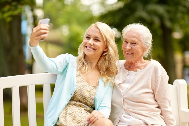 Daughter and senior mother taking selfie at park stock photography