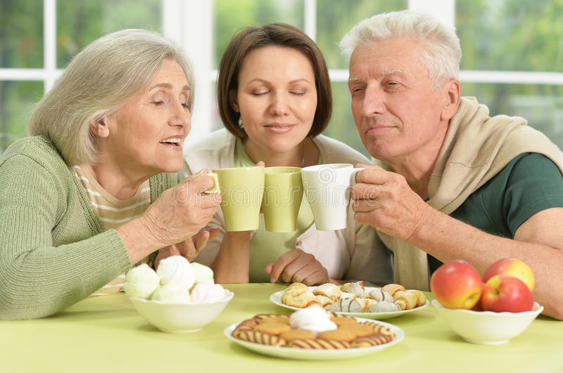 Daughter with senior parents drinkig tea. Cute family portrait , adult daughter with senior parents drinkig tea royalty free stock photo