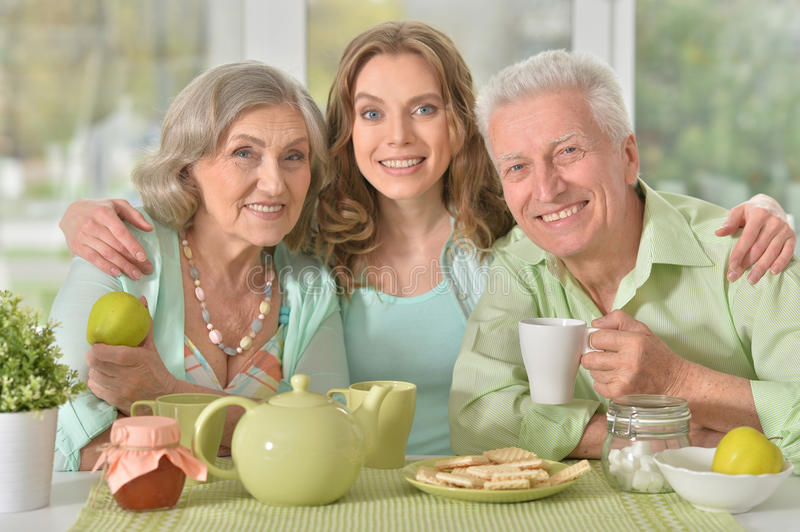 Daughter with senior parents drinking tea. Cute family portrait , adult daughter with senior parents drinking tea royalty free stock photo