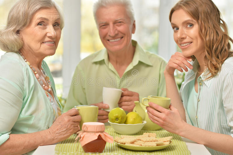 Daughter with senior parents drinking tea. Cute family portrait of adult daughter with senior parents drinking tea stock photography