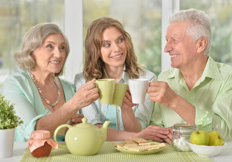 Daughter with senior parents drinking tea. Cute family portrait , adult daughter with senior parents drinking tea royalty free stock images
