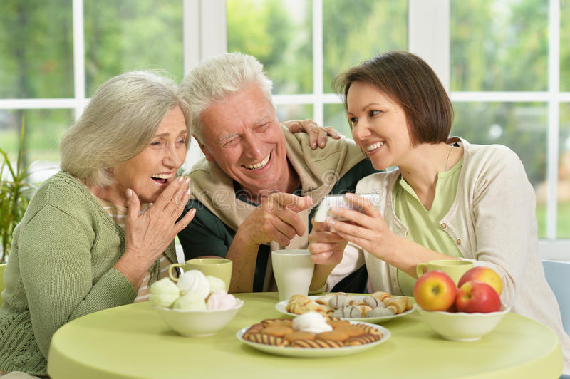 Daughter with senior parents drinking tea. Cute family portrait , adult daughter with senior parents drinking tea stock photos