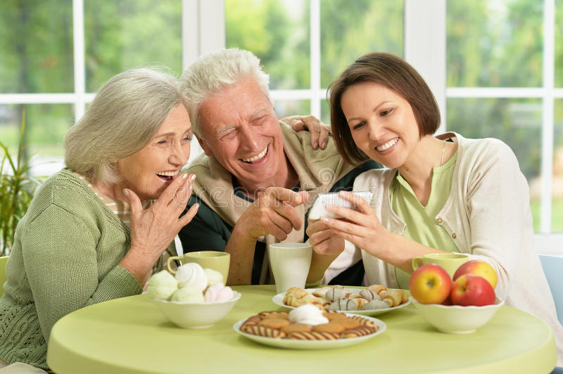 Daughter with senior parents drinking tea. Cute family portrait , adult daughter with senior parents drinking tea royalty free stock image
