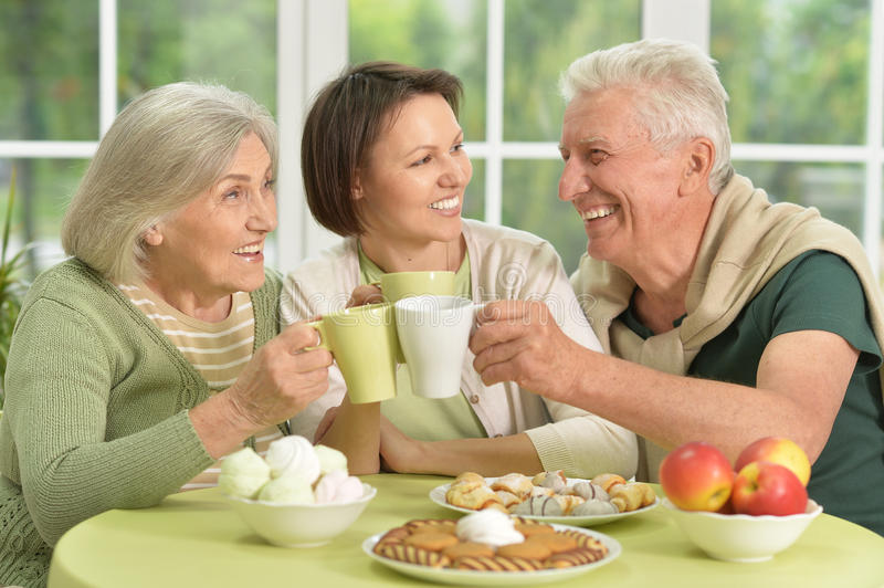 Daughter with senior parents drinking tea. Cute family portrait , adult daughter with senior parents drinking tea stock photography