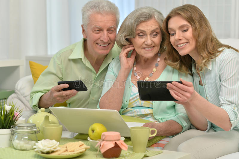 Daughter with senior parents drinking tea. Cute family portrait , adult daughter with senior parents drinking tea and doing selfie royalty free stock images