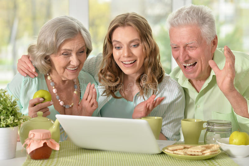 Daughter with senior parents drinking tea. Cute family portrait , adult daughter with senior parents drinking tea with laptop stock photography