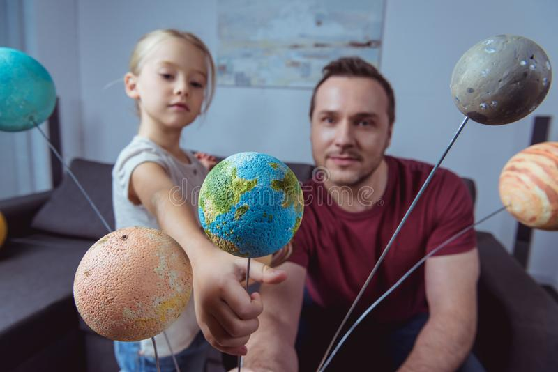Portrait of daughter showing father a miniature of Earth on model of the solar system. At home stock photo