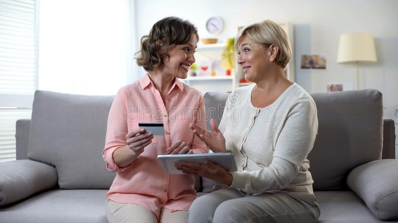 Daughter showing old mother how to pay bills online, holding credit card banking stock image