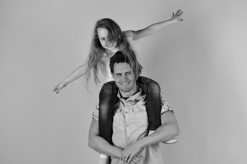 Daughter sits on dads shoulders. Schoolgirl puts hands wide stock photo
