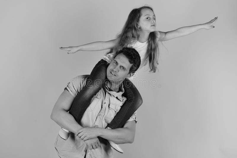 Daughter sits on dads shoulders. Schoolgirl puts hands wide pretending to fly. Girl and man royalty free stock image