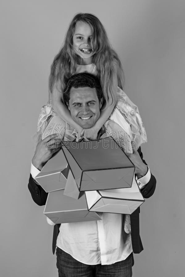 Daughter sits on shoulders. Girl and man with cheerful faces. Daughter sits on dads shoulders. Girl and men with cheerful faces hold shopping bags on pink stock photo