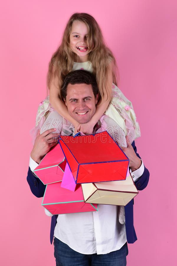 Daughter sits on shoulders. Girl and man with cheerful faces. Daughter sits on dads shoulders. Girl and men with cheerful faces hold shopping bags on pink royalty free stock images